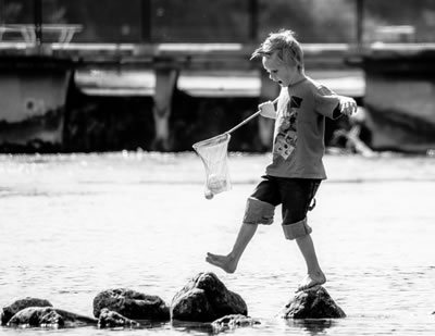 Boy in creek with fishing net: Reconnect with your why & joy