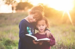 One girl reading to another, one-step-ahead-authority