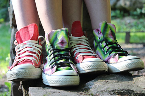 two sets intertwined of unique & colorful converse shoes