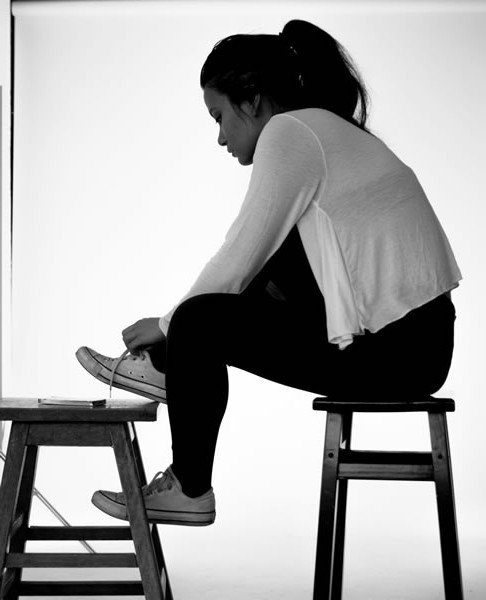 woman on stool lacing up shoes