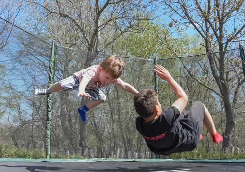 Active pre-teen kids jumping on trampoline